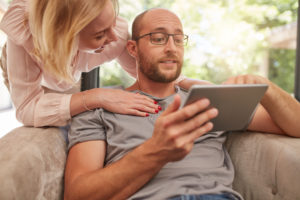 Happy couple at home using digital tablet