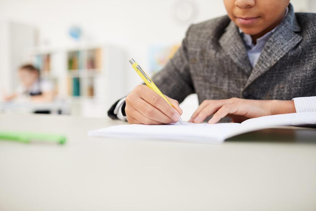 Boy writing in notebook
