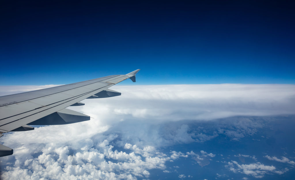 Plane wing on blue sky background